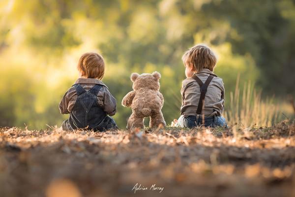 2 bé tạo dáng đáng yêu bên gấu bông