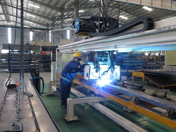 Thanh niên làm việc trong xưởng cơ khí